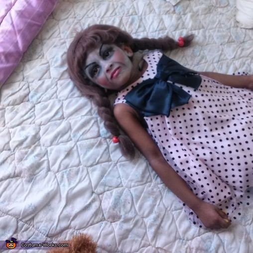 Laying on the bed acting like a doll, Annabelle Doll Costume