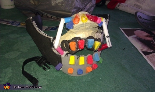 The mask cut up and school supplies glued on, Bane Costume