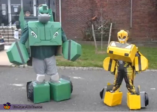 Two power rangers in larger boxy costumes, boxes around their feet and hands protrude out.