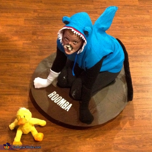 Cat in a Shark Costume riding a Roomba chasing a Duck