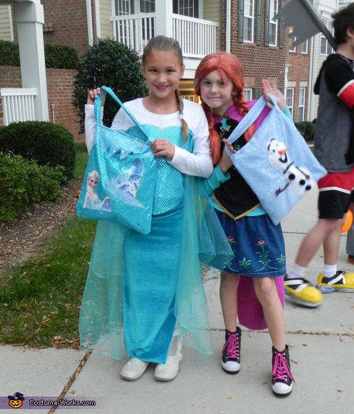 Elsa and Anna posing with their matching candy bags., Elsa and Anna from Frozen Costume