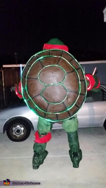 The shell is completely made out of EVA foam.  It was cut in a giant oval in proportion to his body.  Smaller pieces of EVA foam were then used to create details of the shell to show segments.  It was then layered with gesso glue as a 'primer' then paint, Giant Ninja Turtle Raphael Costume