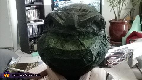 In order to create realism of a turtle, the skin was created with paper towels and barge glue.  This was pieced onto the head frame in layers like papier mache. It was then painted black as seen here, Giant Ninja Turtle Raphael Costume