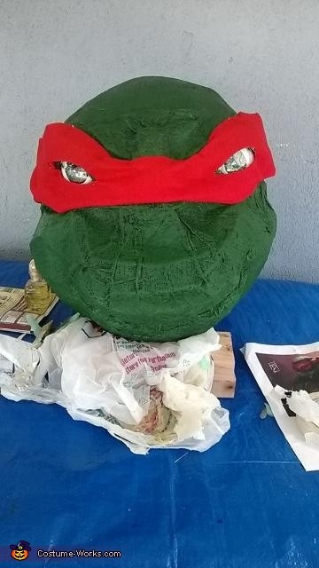 The head was then painted green with acrylics.  For the eyes we used starbuck plastic and painted the iris.  For the mask/bandana red felt was used, Giant Ninja Turtle Raphael Costume