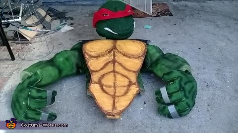 The chest piece was constructed from a thin layer of L200 foam.  Other muscles pieces where carved out of L200 as well.  These were then glued together and painted with gold acrylic and brown for definition, Giant Ninja Turtle Raphael Costume