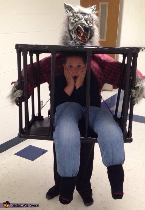 Man carried in a Cage by Werewolf Costume