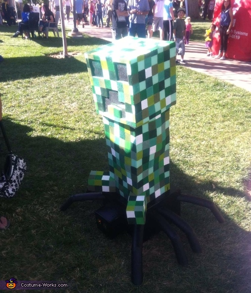 At the Halloween fair with arms tucked inside, Minecraft Boys Costume Creeper riding a Spider