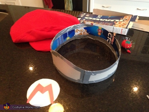 Making the Mario hat from watching Beck Blow video.  Cereal box and duct tape inside to give it shape., Super Mario Costume