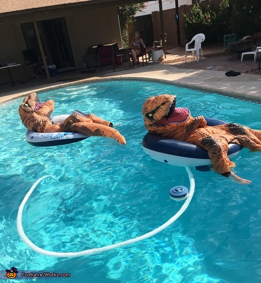 Dad and his friends relaxing in the pool, T-Rex Costume