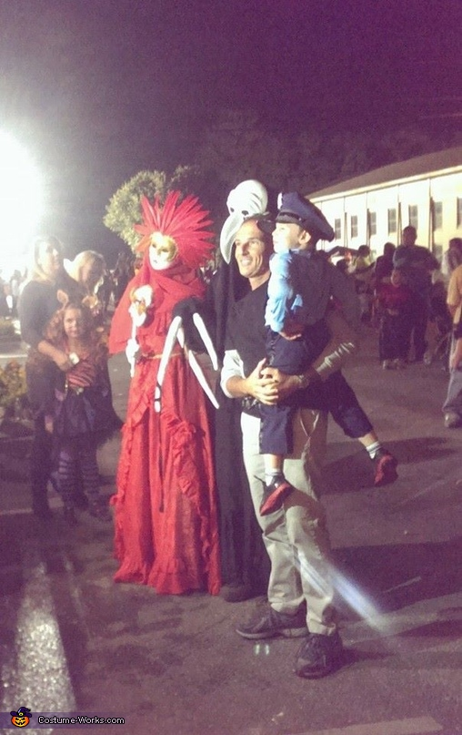a man and the cutest police officer (little boy) take a picture with us while a mom and her litttle girl wait their turn, Venetian Carnival Couple Costume