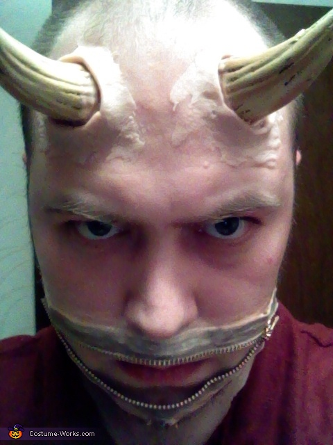 Using scar putty,roll a decent amount between your hands to make two snakes/worms.  Wrap around the base of the horns and kneed gently into your forehead to add depth and realism., Zipper Mouth Demon Costume